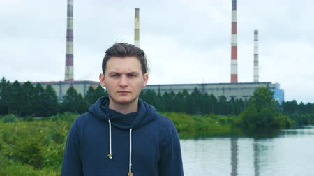 descontente : Portrait of a tired, sleepy, discontented young man standing in the background of the hydroelectric power station and the cloudy sky.