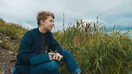 pensamento : A young writer of attractive appearance sits on the river bank and writes a book. In the background, a cattail, an overcast sky and smoking pipes of a hydroelectric power station. Stock Footage
