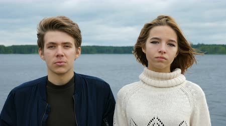 tons : Portrait of two teenagers, a guy and a girl, against the background of a river and forest. Serious and funny attractive faces. Cold tones. Vídeos