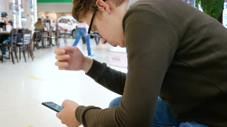 peoples : A young man in glasses uses a mobile phone in a shopping center while his girlfriend is shopping. Stock Footage