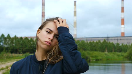 хмурый : Portrait of a young beautiful girl with disheveled hair against the backdrop of a hydroelectric power station building and the overcast sky.