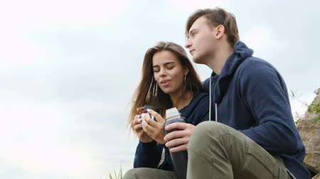 nuvem : The guy and the girl are sitting on the bank of the river, drinking hot tea from a vaccum flask, smiling and enjoying life. Stock Footage