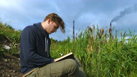 catástrofe : A young man is reading a book on the bank of a river in an industrial city near a cattail. In the background are smoking pipes of an industrial plant and a cloudy sky.