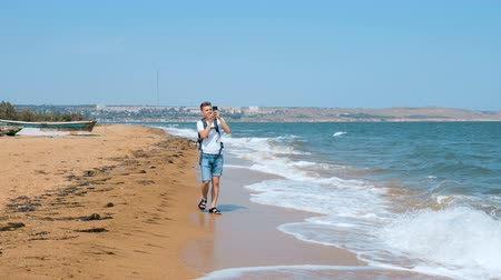 hajtások : A young man with a backpack on his shoulders walks along the sandy beach and takes pictures on his mobile phone. Stock mozgókép