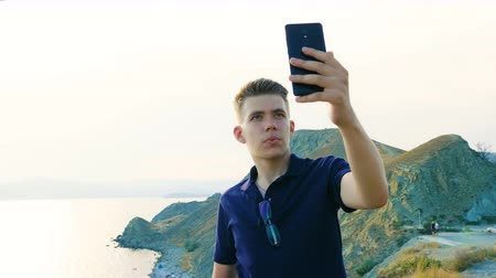 make photo : A young man makes a selfie on the background of the sea, mountains and nature. Stock Footage
