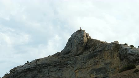 hloupý : A man stands on top of a cliff and shoots nature on a mobile phone.