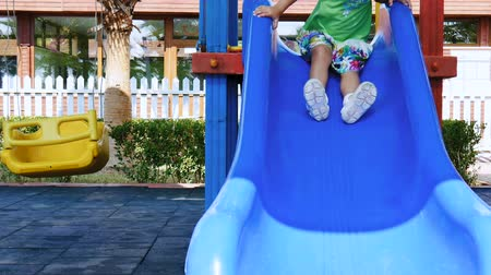 blue braid : Little cute girl sliding down plastic slide on the playground. Stock Footage