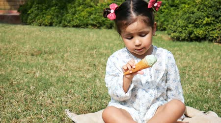 pigtail : Little cute girl eats ice cream sitting on the lawn. Stock Footage