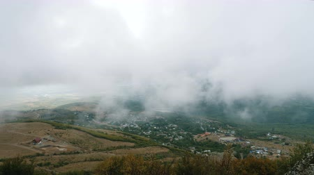thick : Thick dense clouds float over the mountain village in the autumn season.