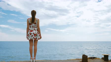 looking distance : A beautiful young pretty girl in a short dress is standing on the pier of the seaport, looking into the distance and waiting for the ship. In the background, a calm sea and a cloudy blue sky.