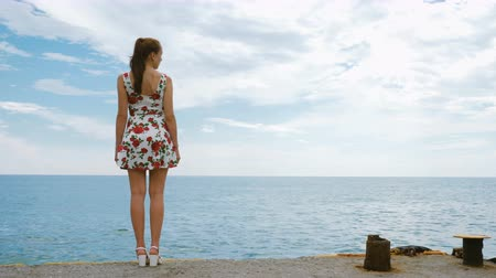 námořník : A beautiful young pretty girl in a short dress is standing on the pier of the seaport, looking into the distance and waiting for the ship. In the background, a calm sea and a cloudy blue sky.
