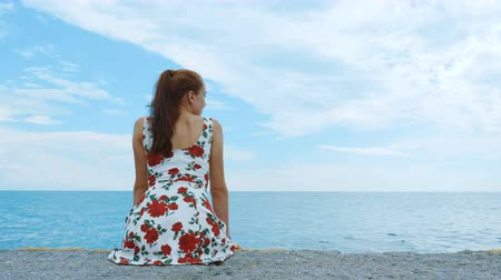 námořník : A beautiful young pretty girl in a short dress is sitting on the pier of the seaport, looking into the distance and waiting for the ship. In the background, a calm sea and a cloudy blue sky. Dostupné videozáznamy