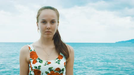 кулон : Portrait. A beautiful young pretty girl in a dress is standing on the pier of the seaport and waiting for the ship. In the background, a calm sea and a cloudy blue sky.
