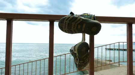 terlik : Lost childrens sandals hang on the railing of the promenade near the sea. Stok Video
