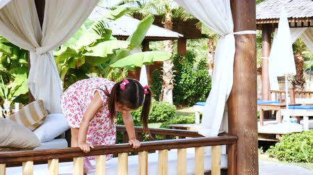 assentos : Little cute girl with pigtails is having fun and jumping on the soft seats of the gazebo. Stock Footage