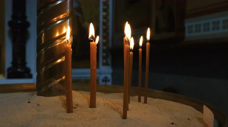 castiçal : Thin candles burning in the church. Candles are in the sand of the candlestick. Close up.