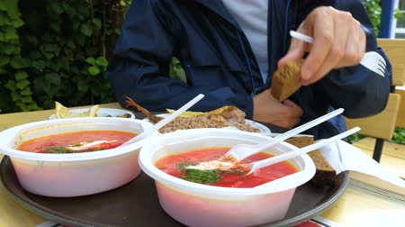 shellfish dishes : A tourist eats borscht, boiled buckwheat, fish, mussels and bread in an open-air summer cafe from plastic dishes.