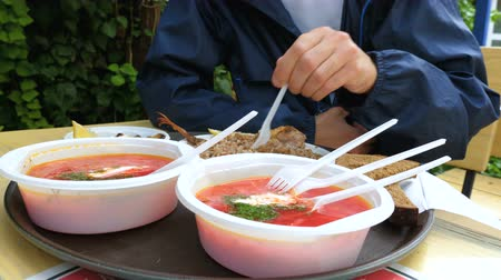 klimop : A tourist eats borscht, boiled buckwheat, fish, mussels and bread in an open-air summer cafe from plastic dishes.