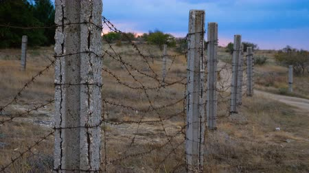запрещенный : The fence of concrete pillars and rusty barbed wire. In the background is the sunset.