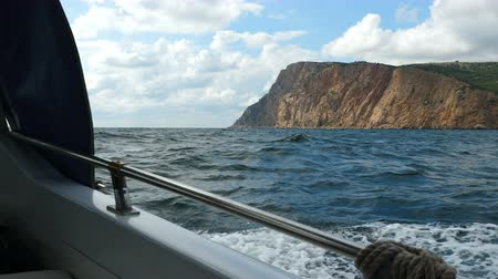 from behind : View from the side of a motor boat on the sea and mountains. The boat swings on the waves. Stock Footage