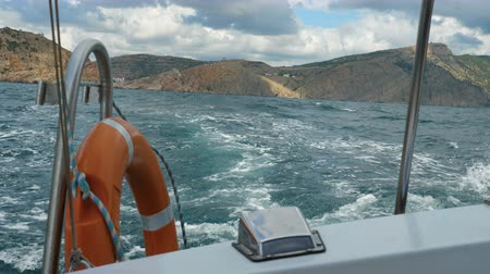 глубоко : View from the side of a motor boat on the sea and mountains. The boat swings on the waves. Стоковые видеозаписи