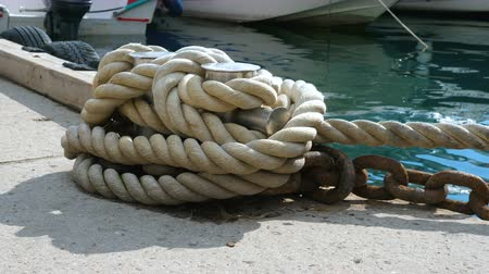 縛ら : Berth port. Bollard with moorings and rusty ship chain. Close up.