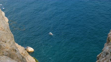 intrigue : A small tourist motor ship sails on the sea near the shore. View from the cliff.