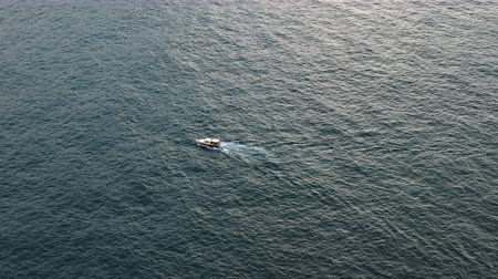 intrigue : The lonely motor boat floats in the open sea.