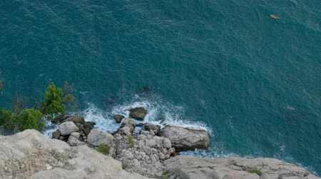 intrigue : Sea waves are breaking on a rocky shore. View from the cliff. Stock Footage