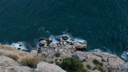 dark island : Sea waves are breaking on a rocky shore. View from the cliff. Stock Footage