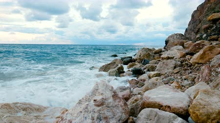 boulders : Sea waves are breaking on a rocky shore. In the background is a blue cloudy sky. Evening time. Stock Footage