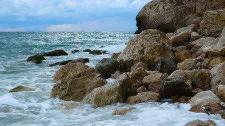 intrigue : Sea waves are breaking on a rocky shore. In the background is a blue cloudy sky. Evening time. Stock Footage