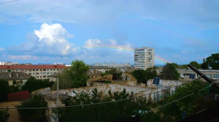 külvárosok : Rainbow disappears over the apartment building. located on the outskirts of the city. Time lapse. Stock mozgókép