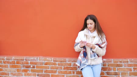 standlar : A young attractive girl stands at the wall of a building and pokes a finger into a mobile phone. In the background are brickwork and a bright red wall.