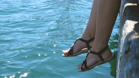 dangle : The girl relaxes sitting on a wooden pier, swing ones feet near the water surface.