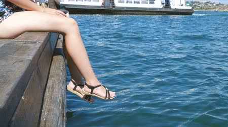 サンダル : The girl relaxes sitting on a wooden pier, swing ones feet near the water surface.