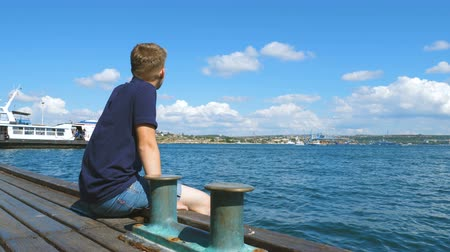 platform edge : A young man is sitting on the pier of the city sea port next to bollards. Stock Footage