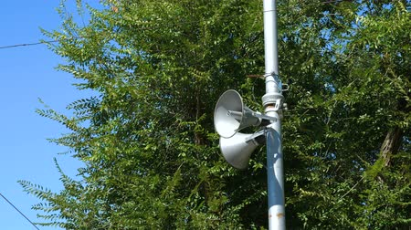 amplificador : Loudspeakers fitted to make announcements on the street pole. In the background dense foliage of trees and blue sky. Close up.