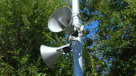 объявлять : Loudspeakers fitted to make announcements on the street pole. In the background dense foliage of trees and blue sky. Close up.