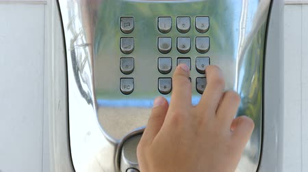 tárcsáz : A young man uses a payphone. The man picks up the phone and presses the buttons with his hand.