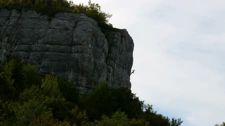 vertical : Climber climbs up a sheer cliff with safety belt and ropes. View from afar.