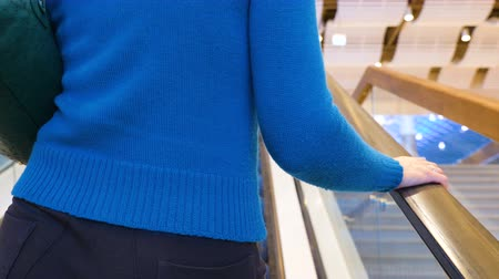 corrimão : Shopping center. A young woman in a blue sweater is standing on an escalator in the mall. Back view. Close up.