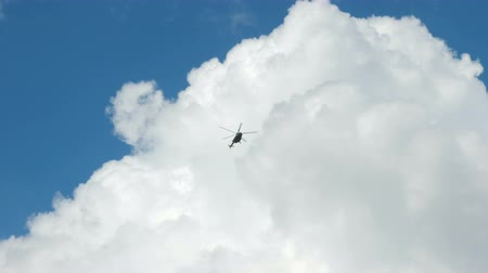 fekete fehér : The helicopter flies against the blue cloudy sky. Stock mozgókép