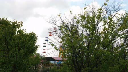 giant wheel : Colorful ferris wheel in an amusement park against the gray sky with clouds. View from afar. Stock Footage