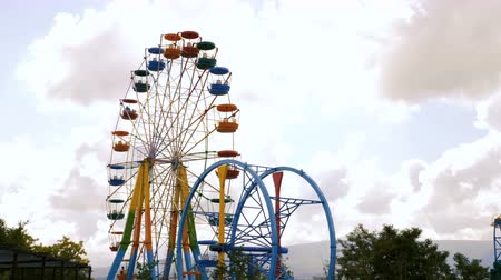 giant wheel : Colorful ferris wheel in an amusement park against the gray sky with clouds.