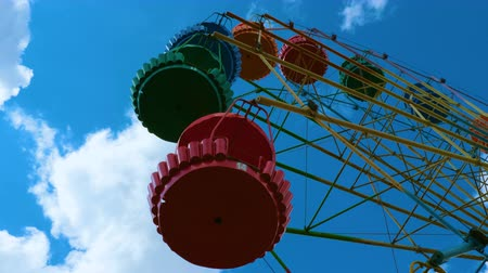 dev : Colorful ferris wheel in an amusement park against the blue sky with clouds. Close up. Stok Video