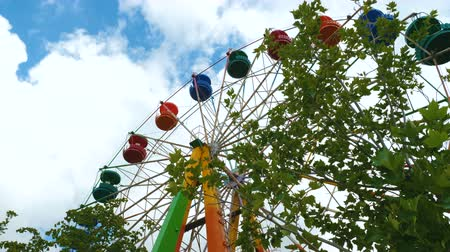 giant wheel : Colorful ferris wheel in an amusement park against the blue sky with clouds. Close up. Stock Footage