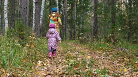 caráter : Mom and daughter are running along the path in the autumn forest.