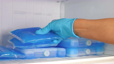 refrigerant : A woman in blue rubber gloves takes an ice pack from the refrigerator. Slow motion. Close up.