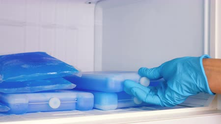 chladič : A woman in blue rubber gloves takes an ice pack from the refrigerator. Slow motion. Close up.